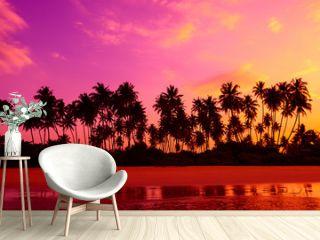 Palm trees on the beach at vivid tropical beach sunset