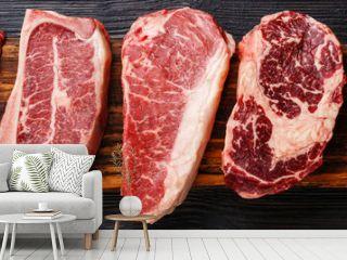 Variety of Raw Black Angus Prime meat steaks Machete, Blade on bone, Striploin, Rib eye, Tenderloin fillet mignon on wooden board