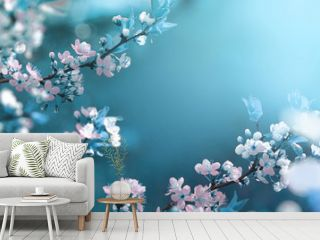 Beautiful floral spring abstract background of nature. Branches of blossoming apricot macro with soft focus on gentle light blue sky background. For easter and spring greeting cards with copy space.