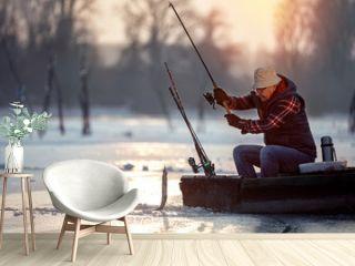 fisherman fishing on ice at the sunrise
