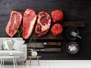 Variety of Raw Black Angus Prime meat steaks Blade on bone, Striploin, Rib eye, Tenderloin fillet mignon on wooden board