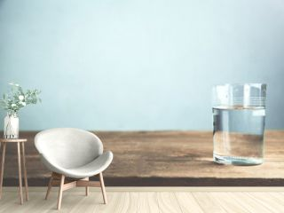 A glass of water on wooden table.