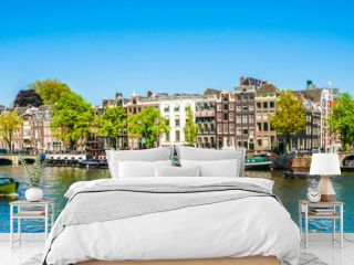 Amsterdam, May 7 2018 - view on the river Amstel filled with small boats and the Magere brug (skinny bridge) in the background on a summer day