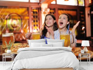 two young pretty girls eating pizza, drinking beer or a beer cocktail and watching football