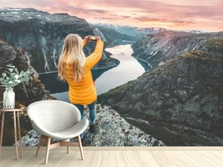 Woman taking photo by smartphone on mountain cliff over lake traveling in Norway adventure lifestyle active vacations modern technology connection concept