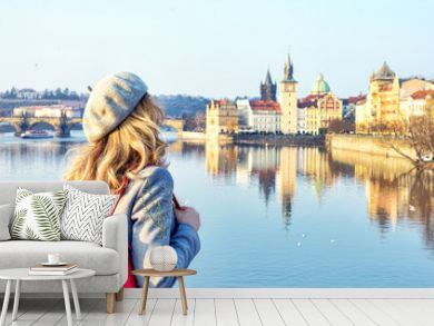 Tourist girl dicovering Prague, Czeh Republic. Charles bridge view on background. Beauty city scape