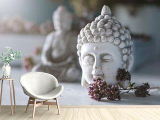 Close up of buddha head with little buddhastatue in the backround in a  zen garden