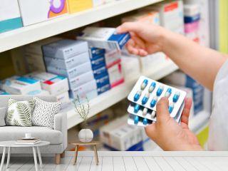 Pharmacist holding medicine box and capsule pack in pharmacy drugstore.