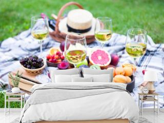 Picnic background with white wine and summer fruits on green grass, summertime party