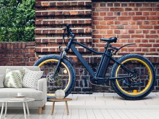 City electric bicycle near a brick wall. Ecological urban transport.