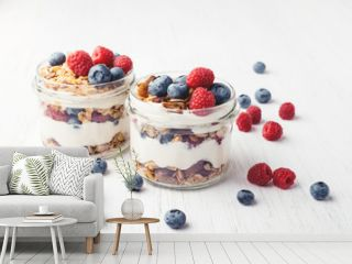 Two jars with granola, berries and yogurt on white wooden table. Shot at angle.