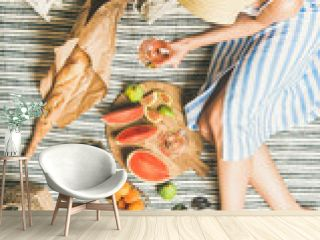 Summer picnic setting. Woman in linen striped dress and straw sunhat with glass of rose wine in hand, fresh fruit and baguette on blanket, top view. Outdoor gathering or lunch
