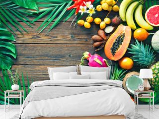 Assortment of tropical fruits with leaves of palm trees and exotic plants on dark wooden background