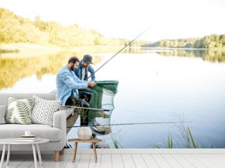 Two happy male friends looking at the fishing net with fish during the fishing on the lake
