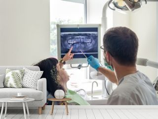 Doctor dentist pointing on patient's X-ray on monitor