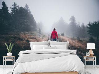 Wanderer läuft in roter Jacke über Schienen im Harz