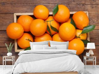 fresh orange fruits in a box on wooden table, top view