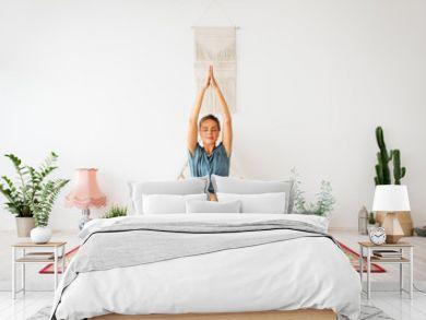 mindfulness, spirituality and healthy lifestyle concept - woman meditating at yoga studio