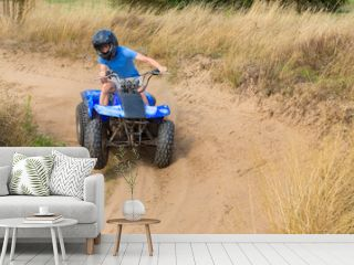 Young man driving quad through curve