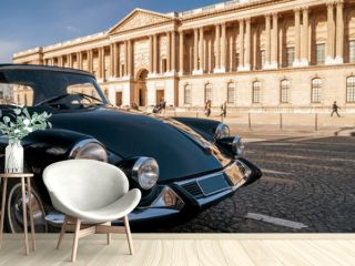 Beautiful black vintage car parked in front of the Louvre Museum, Paris, France