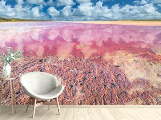 Picturesque shore Pink Salt Lake, Gregory in Western Australia. Blue sky with clouds reflects in Hutt Lagoon between Geraldton and Kalbarri, with a vivid pink color for the presence of algae in summer