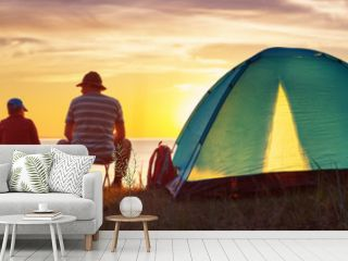 Family resting with tent in nature at sunset