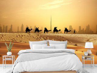 Camel caravan on sand dunes on Arabian desert with Dubai skyline at sunset