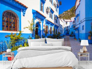 Blue walls of Chefchaouen city medina in Morocco with bright doors and colorful flower pots with sun light.  A magical fairy tale city of heavenly color