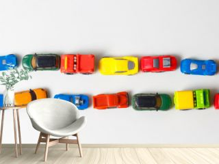 Plastic multi-colored toy cars are lined up on a white background. Stereotypical alignment of subjects is a sign of autism. Selective focus. Copy space for text. Traffic jams air pollution concept.