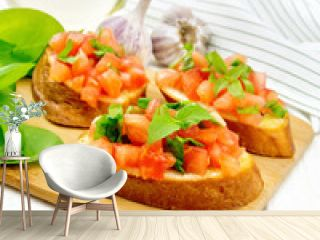 Bruschetta with tomato and spinach on light wooden table