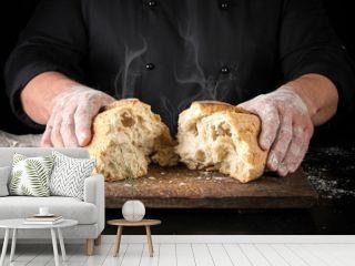 baker in black uniform broke in half a whole baked loaf of white wheat flour bread