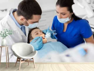 medicine, dentistry and healthcare concept - dentist with mouth mirror and probe checking for kid patient teeth at dental clinic