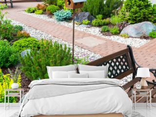 Landscaping in home garden. Beautiful landscape design of yard or backyard in summer. Scenic view of landscaped part with plants and stones.