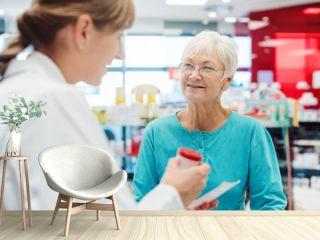 Senior woman in pharmacy talking to the chemist or pharmacist