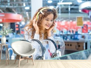 Red-haired girl standing in front of the stand in the electronics store chooses headphones before buying wearing on her head listening to the sound