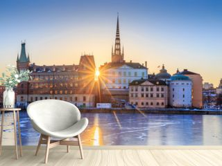 Riddarholmen - part of the historical Old Town (Gamla Stan) in Stockholm, Sweden, at sunrise in winter. Sun star is directly behind the islet and ice is formed on the frozen lake water surrounding it.