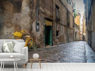 """Street view of an ancient narrow alley (""""caruggio"""" in Genoese) in the historic centre of Genoa with a yellow bicycle parked against a scraped wall and the pavement of stones and bricks, Liguria, Italy"""