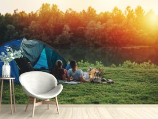 young couple relaxing by the river. camping outdoor