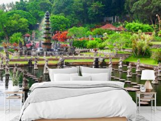 Ancient water palace Tirta Gangga with fountains, natural pools, path in fish pond with statues of dancing women in traditional costumes. Culture, arts of Bali, popular travel destination in Indonesia