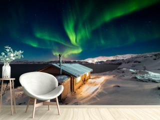 Wooden cottage on the background of the Northern Lights at night.