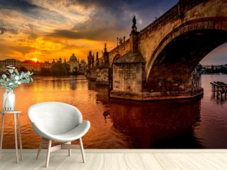 Charles bridge (Karluv most) at sunrise, scenic view of the Old town with Old Town Bridge Tower, colorful sky and historic medieval architecture, Prague, Czech Republic. Holidays in Prague