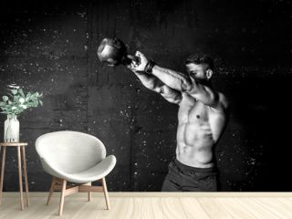 Young strong sweaty focused fit muscular man with big muscles holding heavy kettle bell for swing cross training hard core workout in the gym black and white