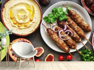 Assorted Middle Eastern and arabic dishes on a dark rustic background,border. Hummus,tabbouleh, salad Fattoush,pita,meat kebab,falafel,baklava,pomegranate. Halal food.Top view, flat lay, copy space