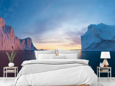 Early morning summer alpenglow lighting up icebergs during midnight season. Ilulissat, Greenland. Summer Midnight Sun and icebergs. Blue ice in icefjord. Affected by climate change and global warming.