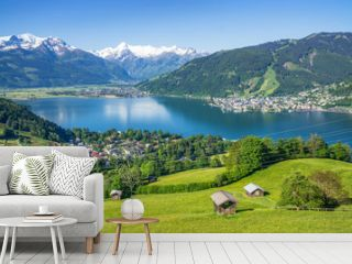 Panoramic view of beautiful scenery in the Alps with clear lake, green meadow, blooming flowers, traditional alpine chalets on a sunny day with blue sky in spring, Zell am See, Salzburger Land, Austri