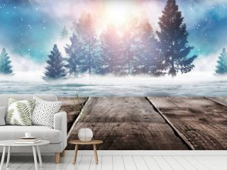 Winter background. Winter snow landscape with wooden table in front. Dark winter forest background at night. Snow, fog, moonlight. Dark neon night background in the forest with moonlight.