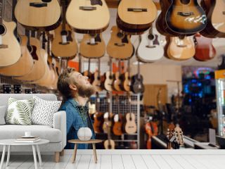 Young guy choosing acoustic guitar in music store