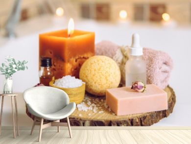 Home spa products on wooden disc tray: bar of soap, bath bomb, aroma bath salt, essential and massage oils, candle burning, rolled towel inside bathroom by tub, water running. Cozy relaxing concept.