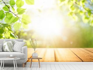Spring beautiful background with green juicy young foliage and empty wooden table in nature outdoor. Natural template with Beauty bokeh and sunlight.