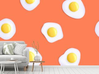 Fried eggs. Seamless pattern. Isolated on an orange background